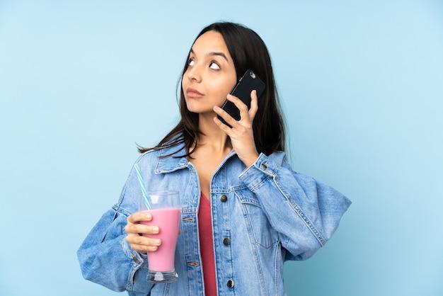 Junge frau mit erdbeermilchshake auf lokalisiertem blauem haltekaffee zum mitnehmen und einem handy