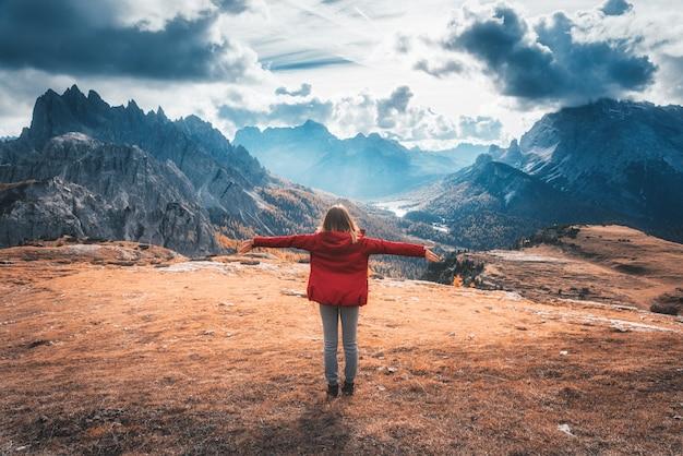 Junge frau mit erhobenen armen und bergen bei sonnenuntergang im herbst in den dolomiten, italien.