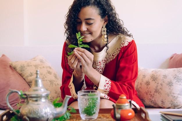 Junge frau mit ethnischen merkmalen, die einen zweig der frischen grünen minze riechen und halten