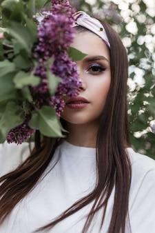 Junge frau mit farbigem make-up im modischen bandana in stilvoller weißer kleidung bedeckt gesicht mit lila blumen des blumenstraußes auf grünen blättern des hintergrundes im park. nettes mädchen des zarten porträts mit lila blumen.