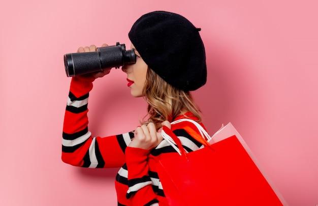 Junge frau mit ferngläsern und einkaufstaschen auf rosa wand