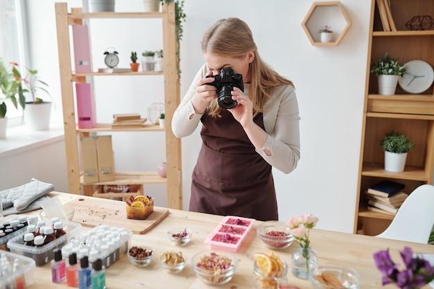 Junge frau mit fotokamera, die bestandteile und aromatisches zeug für die herstellung der handgemachten seife im studio schießt