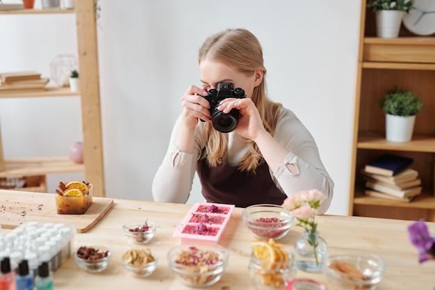 Junge frau mit fotokamera, die handgemachte seife und bestandteile auf tisch im studio fotografiert