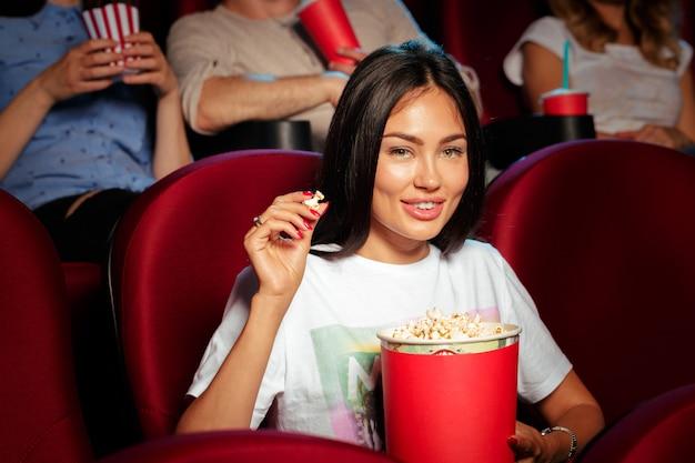 Junge frau mit freunden, die film im kino aufpassen
