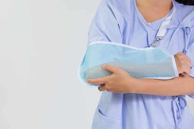 Junge frau mit gebrochenem arm trägt eine armschiene