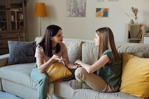 Junge frau mit gelbem kissen, die mit ihrer blonden hübschen tochter probleme im teenageralter bespricht, während sie beide auf der couch im wohnzimmer sitzen?
