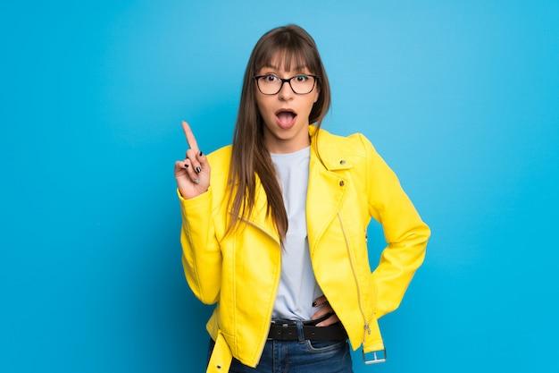 Junge frau mit gelber jacke auf blau eine idee denkend, die oben den finger zeigt