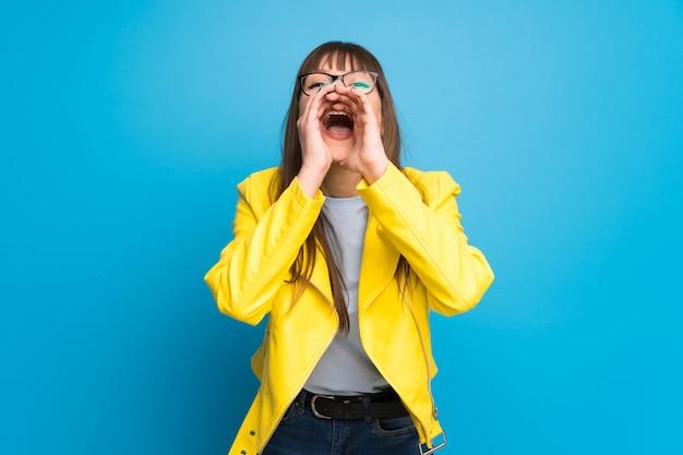 Junge frau mit gelber jacke auf blauem hintergrund etwas schreien und ankündigen