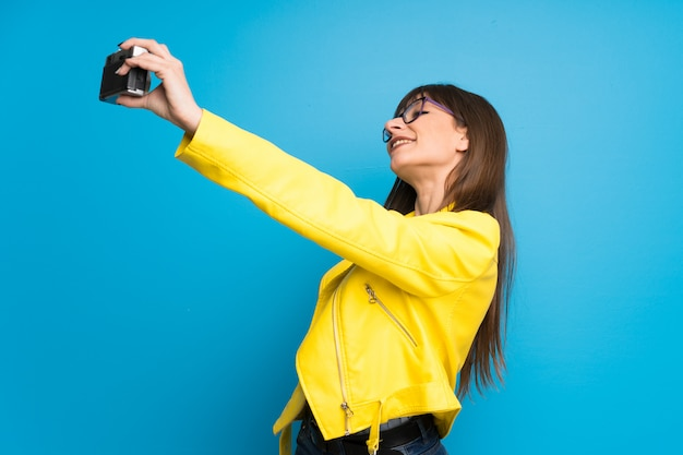 Junge frau mit gelber jacke auf dem blau, das eine kamera hält
