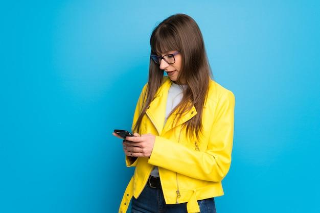 Junge frau mit gelber jacke auf dem blau, das eine mitteilung mit dem mobile sendet