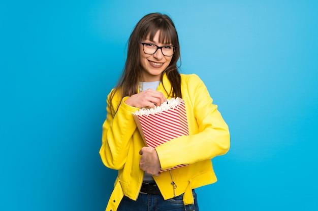 Junge frau mit gelber jacke auf dem blau überrascht und popcorn essend