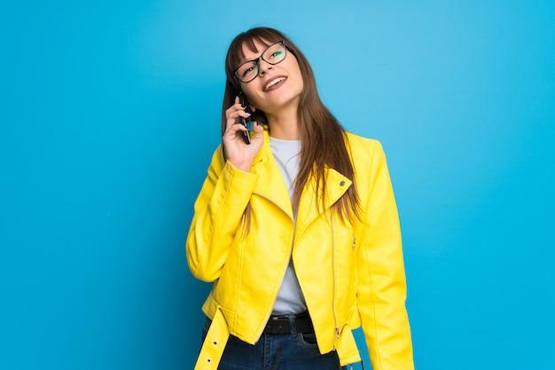 Junge frau mit gelber jacke auf dem blauen hintergrund, der ein gespräch mit dem handy hält
