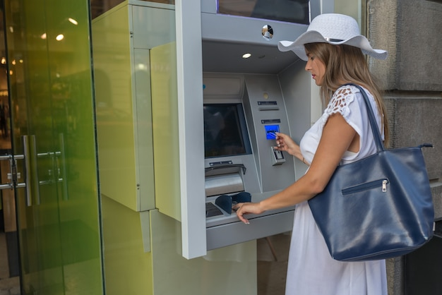 Junge frau mit geldautomaten