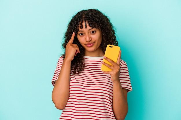 Junge frau mit gemischten rassen, die ein mobiltelefon isoliert auf blauem hintergrund hält und mit dem finger auf den tempel zeigt, denkt, konzentriert sich auf eine aufgabe.