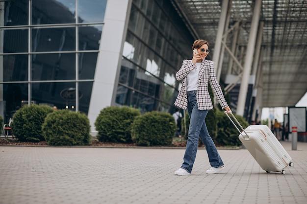 Junge frau mit gepäck am flughafen reisen und telefonieren