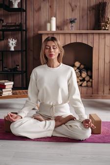 Junge frau mit geschlossenen augen, die auf dem teppich sitzt und im raum meditiert. gesundes und lifestyle-konzept