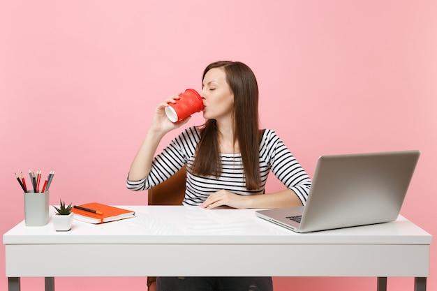 Junge frau mit geschlossenen augen trinkt kaffee oder tee aus der tasse, genießt die arbeit an einem projekt, das im büro mit einem pc-laptop sitzt