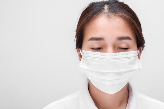 Junge frau mit gesichtsmaske auf weißem hintergrund isoliert, um coronavirus & pm 2.5 luftverschmutzung zu verhindern, frau demonstrieren, wie man virusschutzgesichtsmaske trägt.