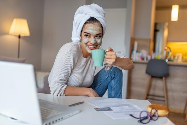Junge frau mit gesichtsmaske wendete das kaffeetrinken an, während laptop verwendet.