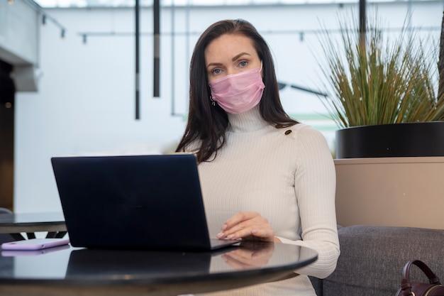 Junge frau mit gesichtsschutzmaske arbeitet am laptop im café...