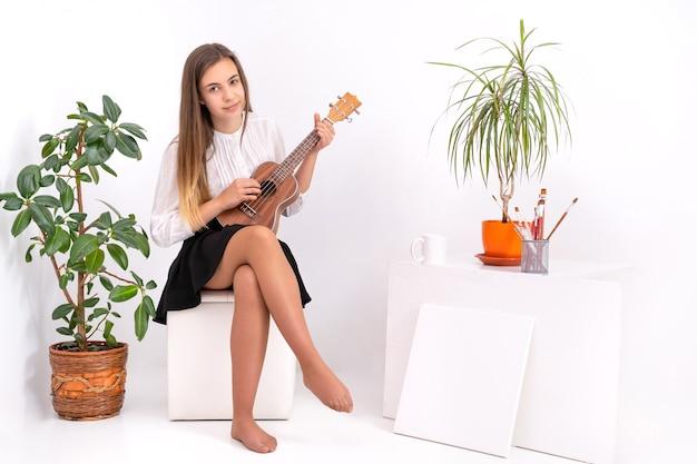 Junge frau mit gitarre auf weißem hintergrund mit kopienraum