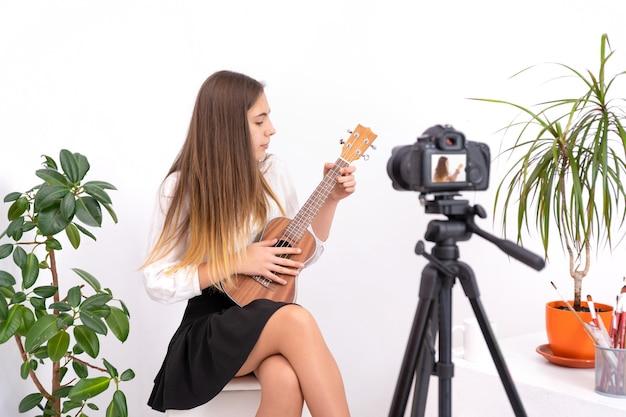 Junge frau mit gitarre, die online-inhalt auf weißem hintergrund mit kopienraum schafft