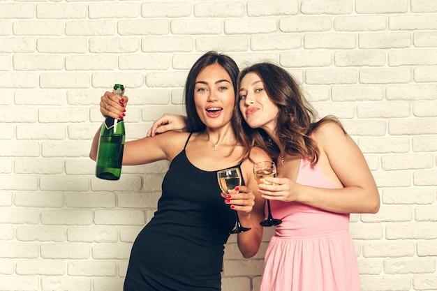 Junge frau mit gläsern eines champagners an der feier