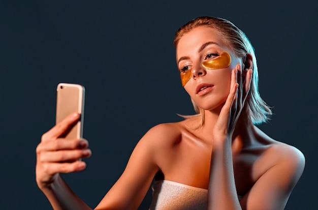 Junge frau mit goldenen augenflecken und telefon in der hand