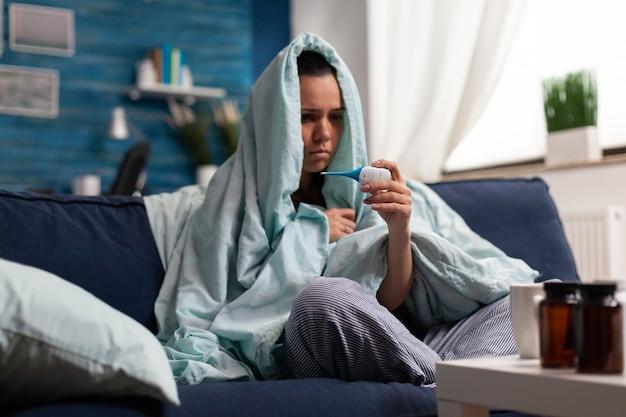 Junge frau mit grippesymptomen bei der temperaturkontrolle