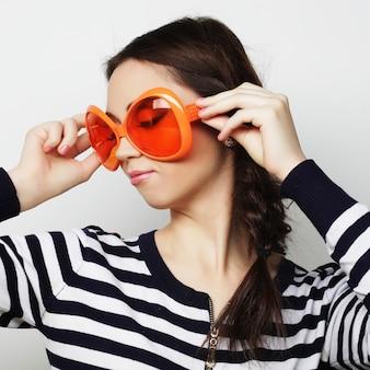 Junge frau mit großer orange sonnenbrille