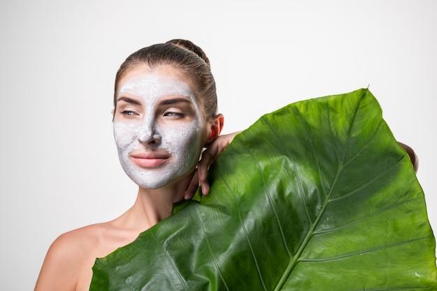 Junge frau mit grüner gesichtsmaske - natürliches spa, schönheit vom naturkonzept