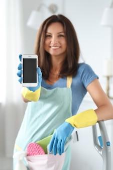 Junge frau mit gummihandschuhen, die smartphone zeigen
