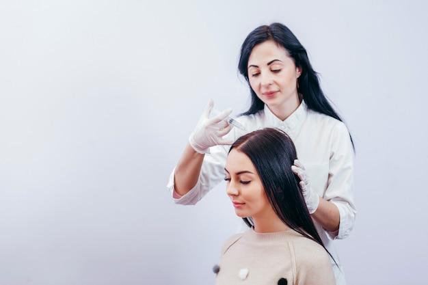 Junge frau mit haarausfallproblem, das injektion erhält, nahaufnahme