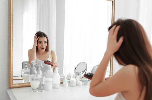 Junge frau mit haarausfallproblem vor dem spiegel zu hause
