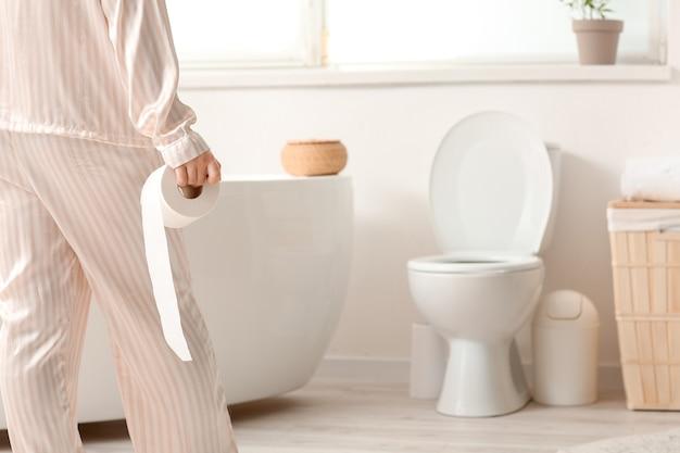 Junge frau mit hämorrhoiden, die badezimmer besuchen