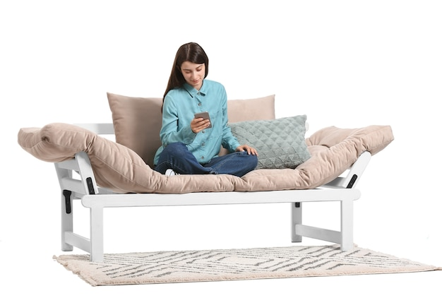 Junge frau mit handy sitzt auf sofa vor weißem hintergrund