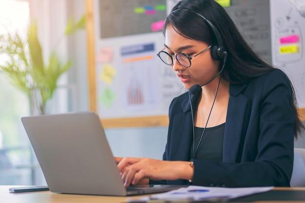 Junge frau mit headset arbeitet im callcenter-betreiber videoanruf vor monitor