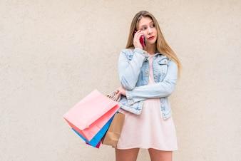 Junge Frau mit hellen Einkaufstaschen telefonisch sprechend