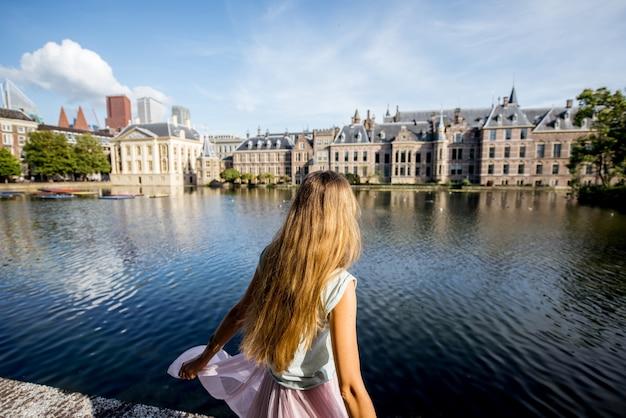 Junge frau mit herrlichem blick auf den see und die alten gebäude im zentrum der stadt haag in den niederlanden