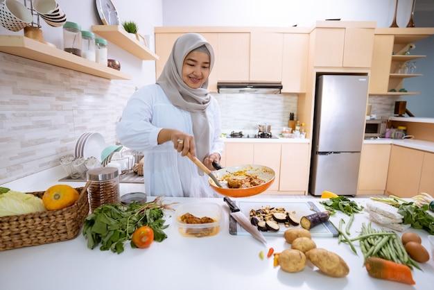 Junge frau mit hijab, der in ihrem haus mit moderner küche zum abendessen kocht