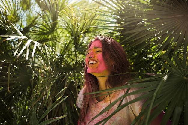 Junge frau mit holi farbe auf ihrem gesicht, das nahe der grünpflanze steht
