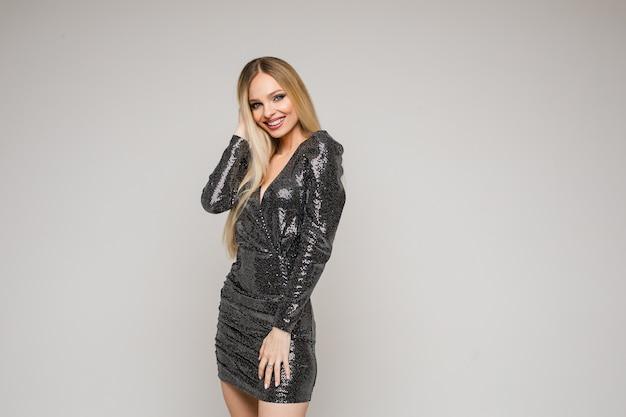 Junge frau mit hübschem gesicht mit langen blonden haaren posiert für das modemagazin im kurzen schwarzen glänzenden kleid