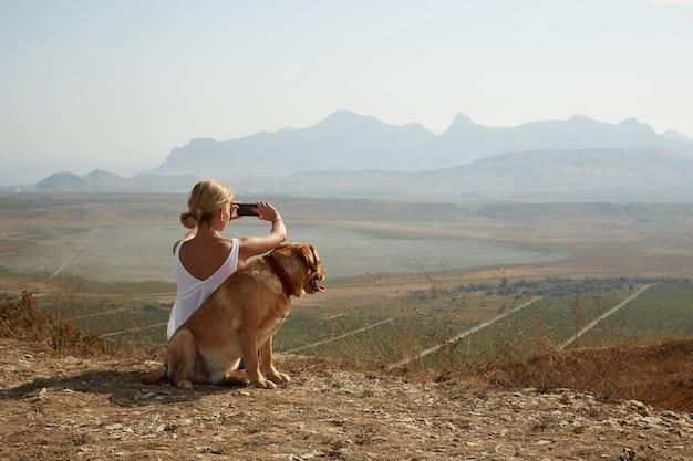 Junge frau mit hund an einem sonnigen tag, der auf hohen bergen sitzt