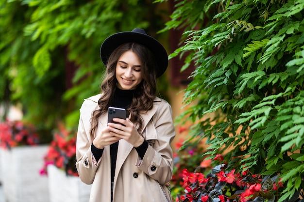 Junge frau mit hut geht in die stadt und benutzt ein smartphone. hipster auf einem spaziergang benutzt das telefon und macht fotos für soziale netzwerke