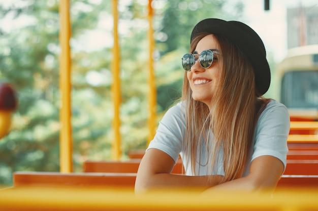 Junge frau mit hut und sonnenbrille auf einer stadtrundfahrt