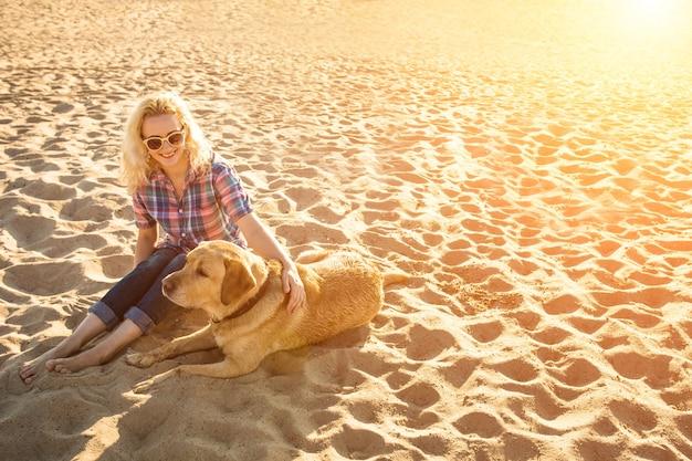 Junge frau mit ihrem hund am strand sonneneruption