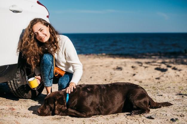 Junge frau mit ihrem hund am strand