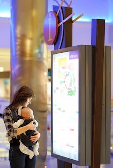 Junge frau mit ihrem kleinen baby in einem einkaufszentrum