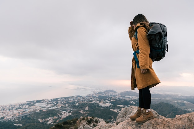 Junge frau mit ihrem rucksack, der auf die oberseite des berges idyllische ansicht betrachtend steht