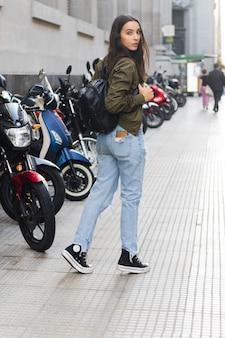 Junge frau mit ihrem rucksack gehend auf bürgersteig
